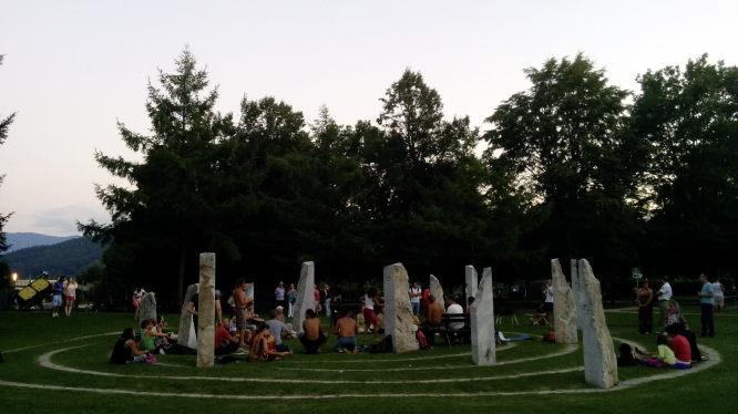 Das Drum & Dance im Steinkreis im Klagenfurter Europapark. Menschen stehen und sitzen zusammen in einem modernen Steinkreis und machen zusammen Musik. Einige tanzen.